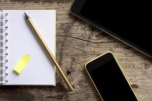 tablet, telefono e blocco note sul tavolo di legno foto