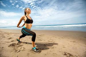 giovane donna che si estende sulla spiaggia foto