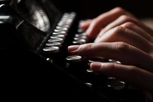 mani che scrivono sulla vecchia macchina da scrivere su sfondo di legno foto