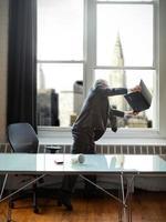 uomo d'affari frustrato che getta un computer portatile fuori dalla finestra foto