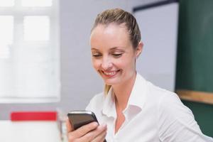 donna di affari sorridente bionda che per mezzo dello smartphone foto