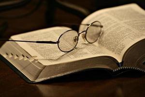 occhiali appoggiati su una pagina di un libro aperto foto