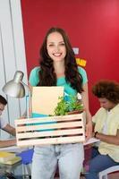 donna di affari casuale che trasporta i suoi effetti personali in scatola foto