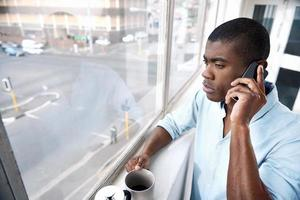 uomo africano del telefono del caffè foto