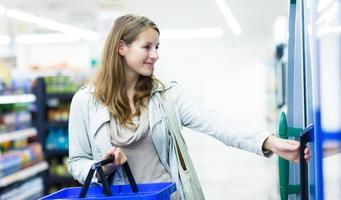 bella giovane donna shopping in un negozio di alimentari foto