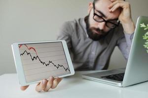 uomo d'affari depresso da un cattivo grafico del mercato azionario foto