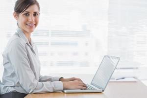 imprenditrice digitando sul suo computer portatile e sorridente
