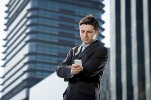 uomo d'affari che parla sul distretto finanziario del telefono cellulare all'aperto nello stress foto