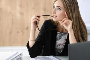 giovane bella donna d'affari seduto al suo posto di lavoro foto