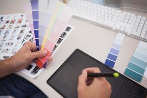 designer con tavoletta grafica e cartelle colori foto
