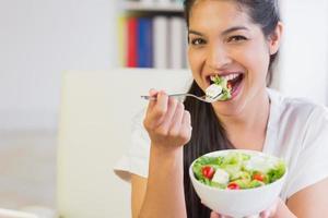 donna di affari felice che mangia insalata sana foto