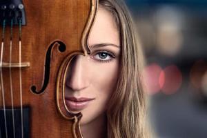 bella giovane donna che dà una occhiata dietro il violino foto