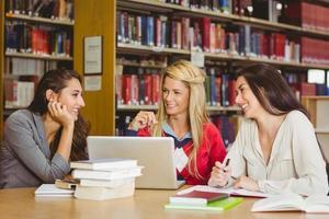 studente maturo sorridente con i compagni di classe che utilizza computer portatile foto