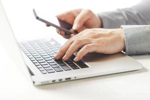 Chiuda sull'immagine dell'uomo di affari che scrive sul computer portatile foto