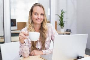 donna di affari allegra che per mezzo del suo taccuino che tiene una tazza foto