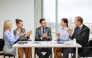 squadra di affari con le mani d'applauso del computer portatile