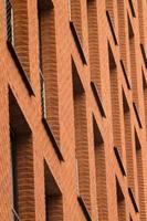muro di mattoni arancione con finestre di edificio moderno