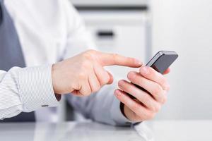 mano maschile in possesso di un telefono cellulare e la scrittura foto