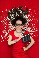 bella ragazza con occhiali da cinema 3d, popcorn e assicella regista foto