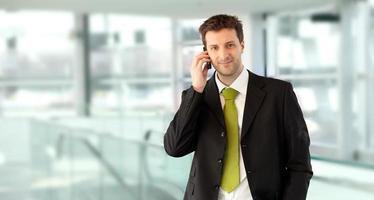chiamata del giovane direttore aziendale con il telefono cellulare foto