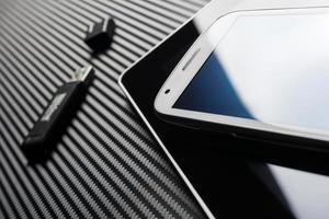smartphone bianco su tablet accanto all'unità USB su carbonio foto