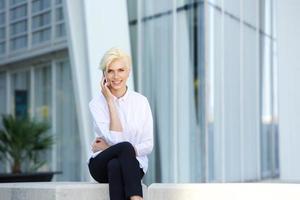 donna sorridente di affari che si siede fuori con il telefono cellulare foto