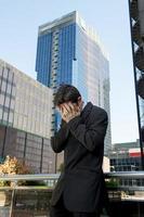 uomo d'affari preoccupato che sta all'aperto nello stress e nella depressione foto