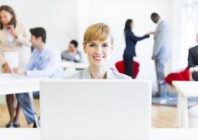 donna caucasica di affari che sorride mentre lavorando al suo computer portatile foto