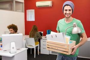 uomo d'affari casuale che trasporta i suoi effetti personali in scatola foto