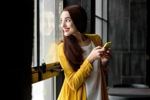 donna che per mezzo del telefono foto