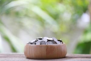 moneta d'argento in ciotola di legno. foto