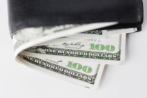 stretta di denaro dollaro USA nel portafoglio sul tavolo foto