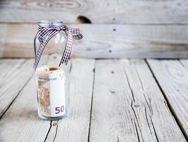 soldi in barattolo di vetro sul tavolo di legno foto