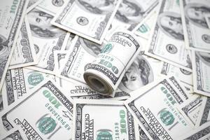 concetto di denaro. rotolo di dollari contro molti altri. foto