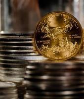 noi aquila d'oro riposa tra pile di monete d'argento foto