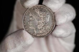 tenuto in mano la moneta del dollaro d'argento di Morgan