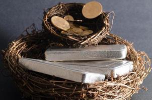 nidificare uova di monete d'oro e lingotti d'argento foto
