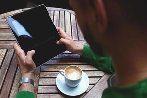 maschio con touch pad per lavoro remoto durante la colazione del mattino foto