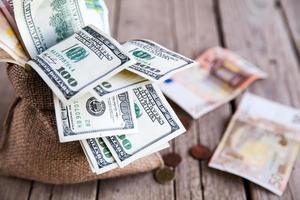 soldi in tela di sacco e monete sparse su un fondo di legno foto