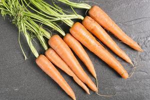 carote fresche su ardesia nera foto