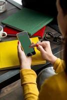 donna vestita di giallo usando il suo smartphone foto