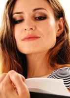 giovane donna che legge un libro isolato su bianco foto