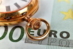 orologio da tasca dorato ed euro foto