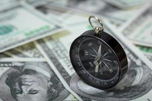 bussola posizionata su banconote da un dollaro americano foto