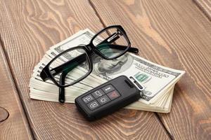 denaro contante, occhiali e chiave a distanza per auto foto
