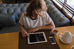 giovane donna che lavora su tavoletta digitale durante la pausa caffè foto