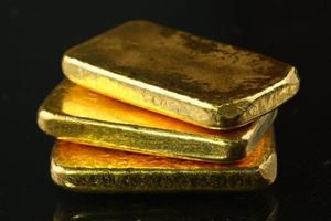 lingotto d'oro messo sullo sfondo scuro. foto