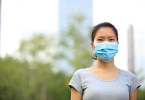 giovane donna che indossa la maschera sulla città foto