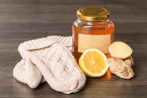 miele, limone, zenzero e guanti su un fondo di legno foto