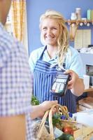 cliente che paga per lo shopping usando la macchina della carta di credito foto